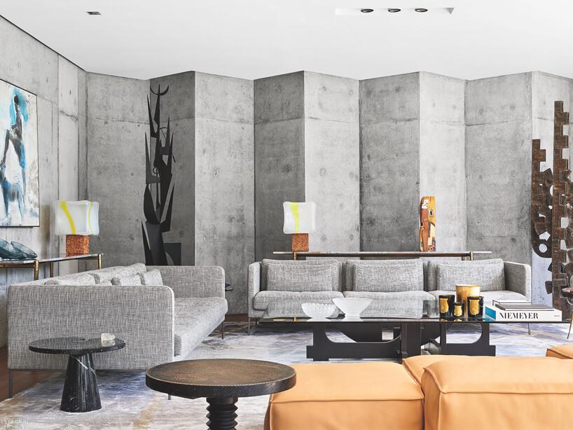 szary salon zbetonową ścianą wkształcie trójkątów zbiałym sufitem
