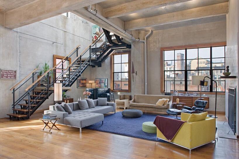 nowoczesne dwupoziomowe mieszkanie zbetonowymi ścianami zdrewnianymi podłogami iczarnymi metalowo drewnianymi schodami