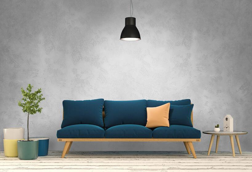 drewniana ławka zniebieskimi poduszkami na tle szarej ściany