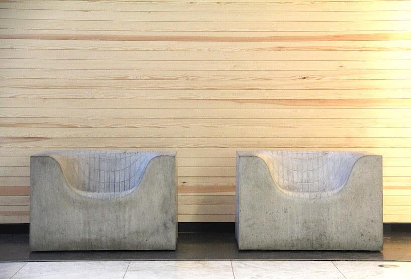 dwa betonowe fotele na tle drewnianej ściany