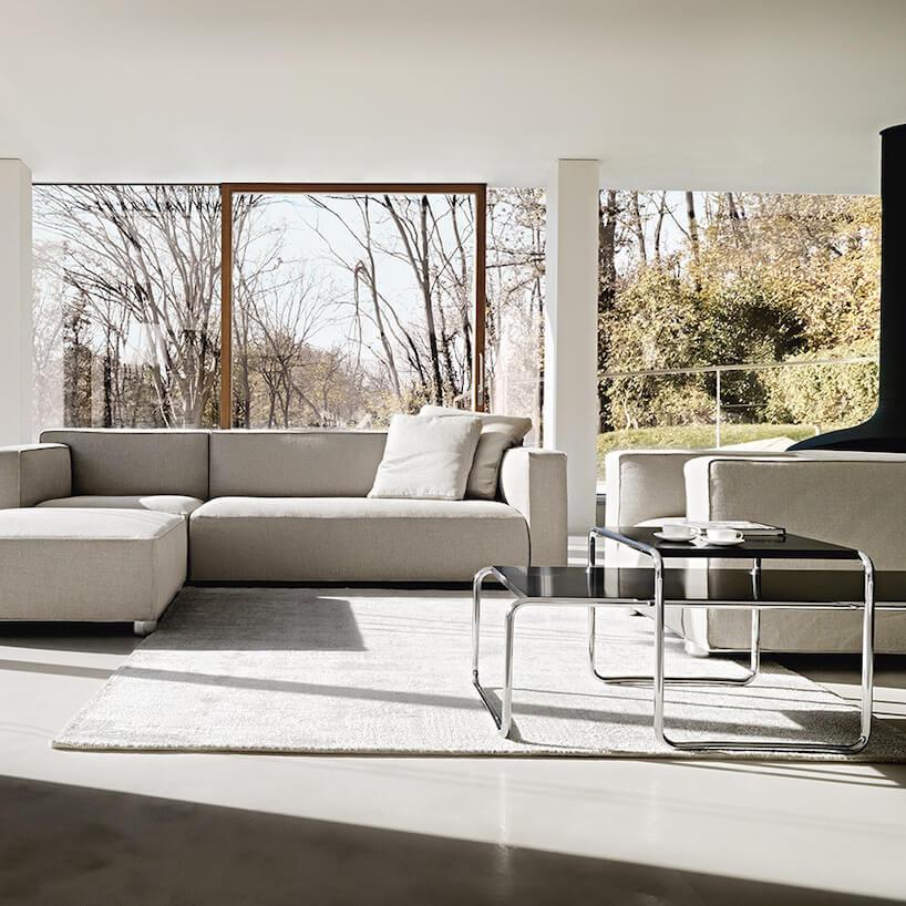 eleganckie szare wnętrze salonu zszarą sofą na tle panoramicznych okien zwidokiem na las