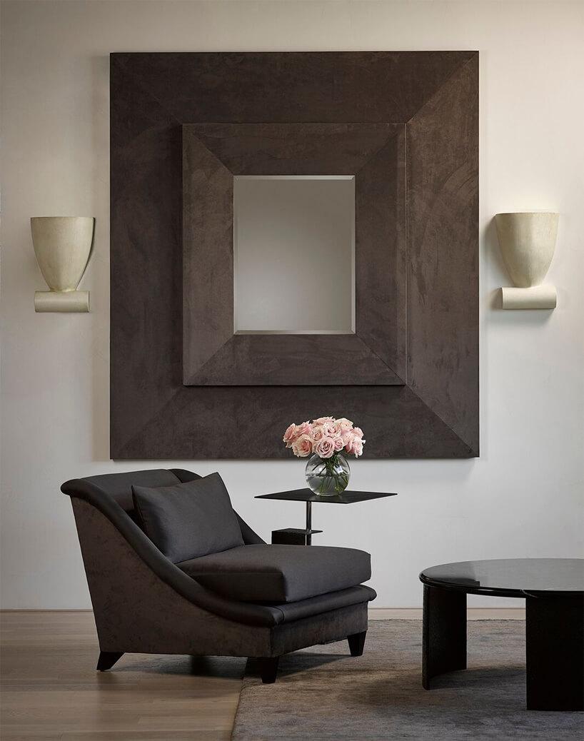 eleganckie lustro zgrubą brązową ramą wiszace na brązowym niskim fotelem