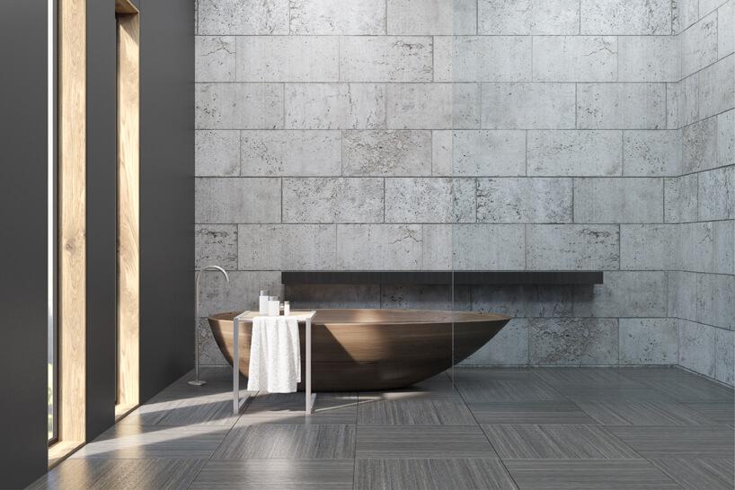 zdjęcie szarej łazienki zbrązową wanną ze ścianą zbetonowych pustaków