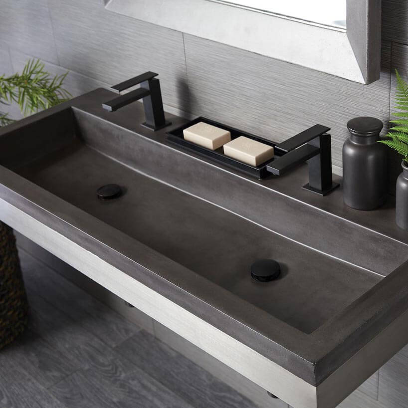 czarna betonowa umywalka wszarej łazience zczarnymi bateriami