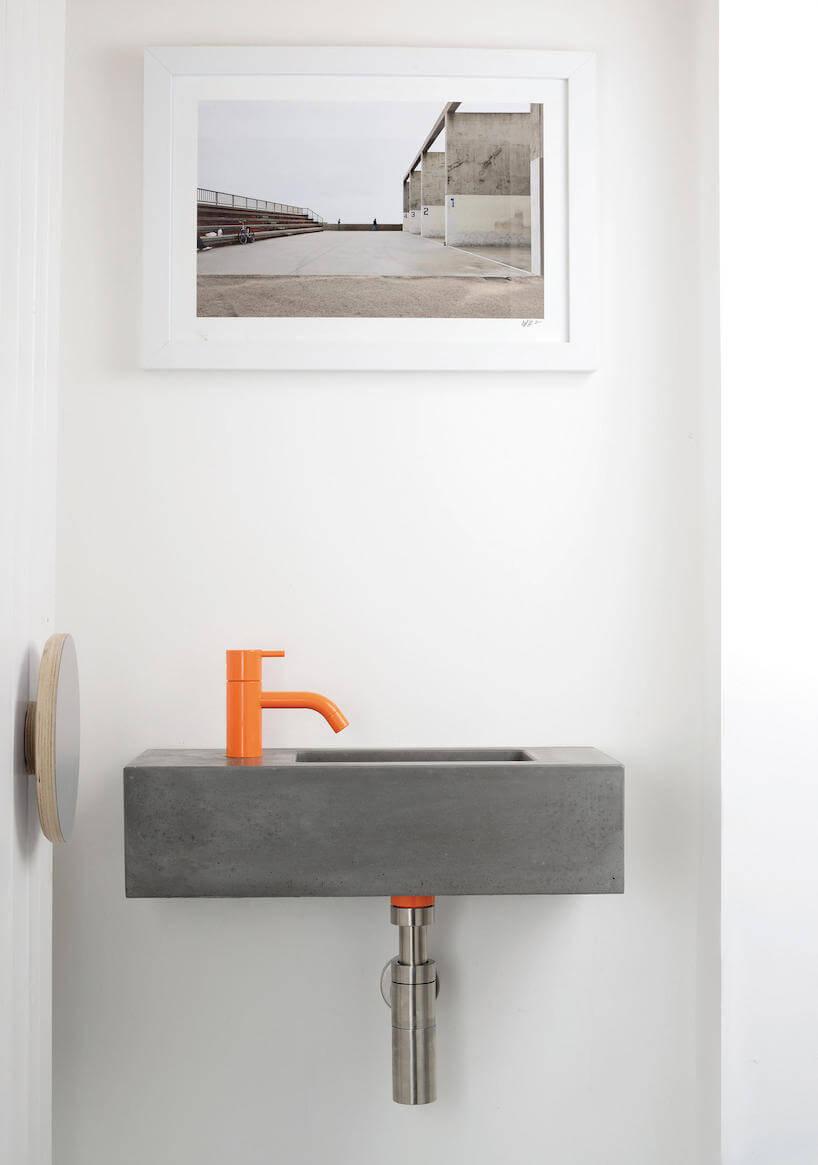 szara betonowa umywalka zpomarańczową baterią wbiałej łazience