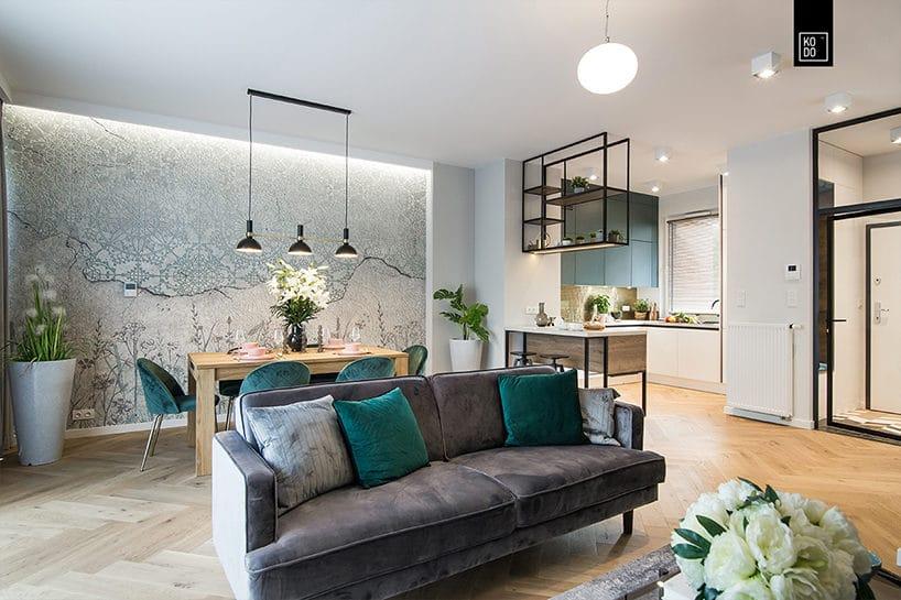 otwarty salon zdrewnianą podłogą dużą sofą pośrodku na tle drewnianego stołu jadalnego
