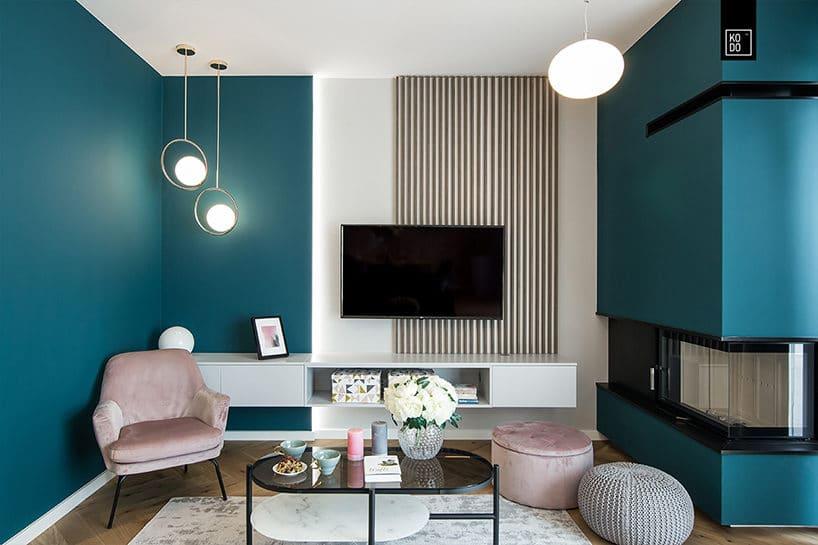 elegancki mały salon zkominkiem narożnym zjaskrawą niebieską ścianą zdrewnianym parkietem