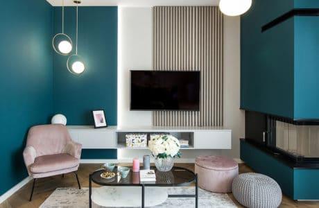 elegancki mały salon z kominkiem narożnym z jaskrawą niebieską ścianą z drewnianym parkietem