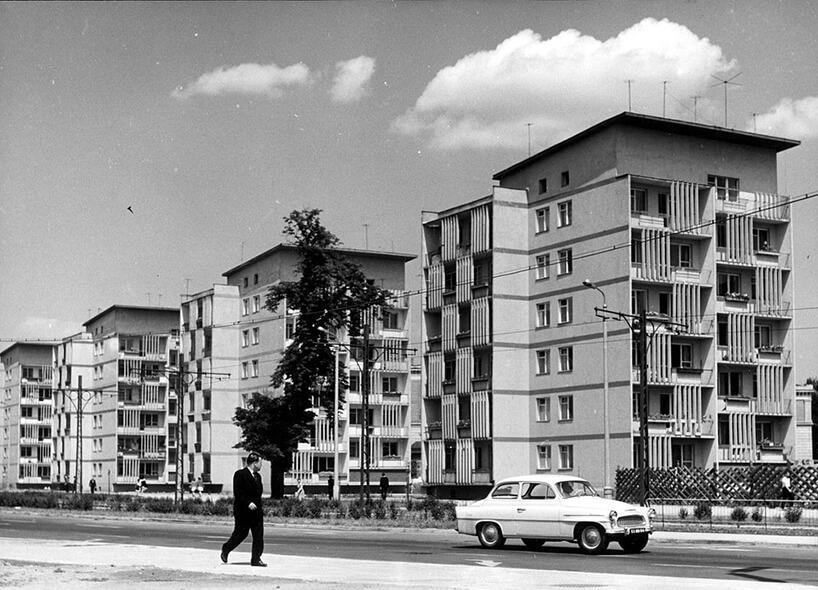 stare czarno-białe zdjęcie zbiałym starym samochodem na tle niedużych bloków mieszkalnych