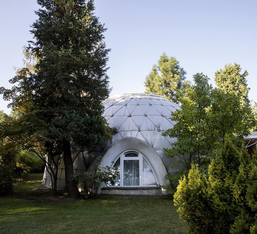 wyjątkowy mały budynek wkształcie kopuły zowalnym oknem pośród drzew