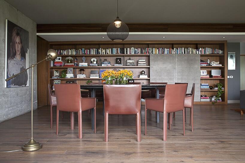 krzesła wbrązowej skórze wokół czarnego stołu na drewnianej podłodze