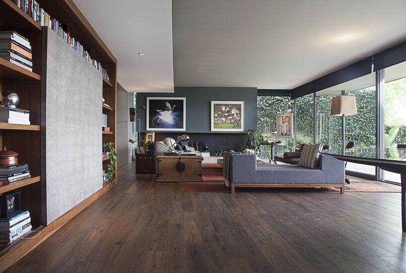 duży nowoczesny przeszklony salon ciemno brązową drewnianą podłogą