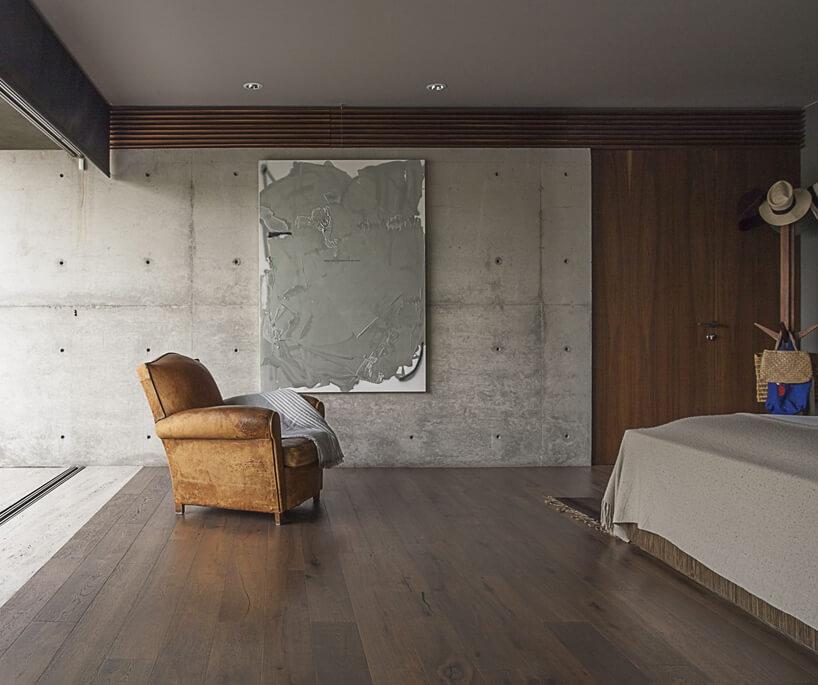 duża sypialnie zdużym łóżkiem ifotelem na tle betonowej ściany