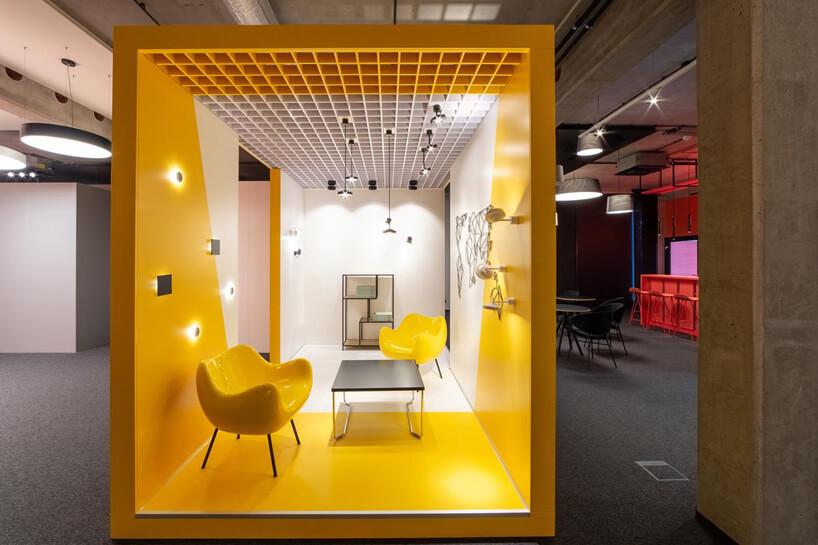 aranżacja wnętrza biało żółtego salonu znietypowymi żółtymi krzesłami iniskim czarnym stolikiem