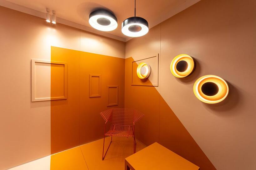 pomarańczowa aranżacja salonu zsiatkowym krzesłem iokrągłymi lampami
