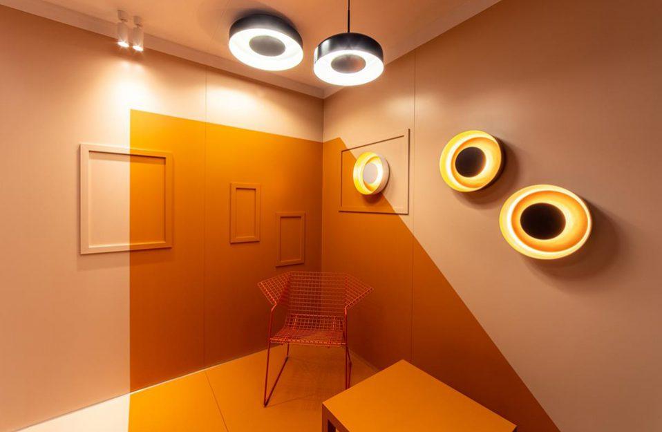 pomarańczowa aranżacja salonu z siatkowym krzesłem i okrągłymi lampami