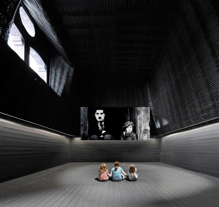 ciemne pomieszczenie zdużym ekranem idziećmi