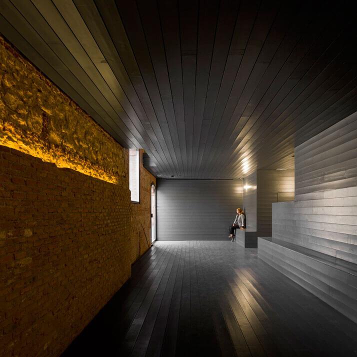 korytarz zciemnych desek zjasną ceglaną podświetlną ścianą