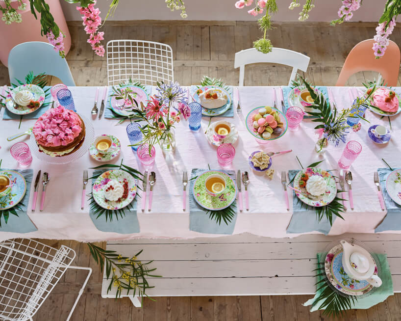 długi zastawiony stół przykryty białym obrusem iwiszące nad nim kwiaty cięte