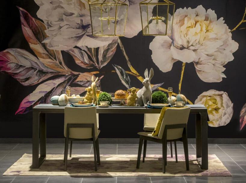 mały stół zdodatkamai wielkanocnymi na tle ciemnej ściany zgrafiką kwiatów