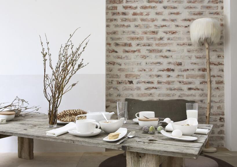 minimalistycznie zastawiony stary drewniany stół na tle starej ceglanej ściany