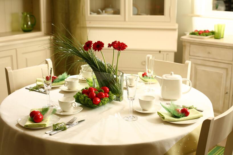 mały okrągły zastawiony stół białą zastawą udekorowany czerwonymi jajkami wbiałej kuchni