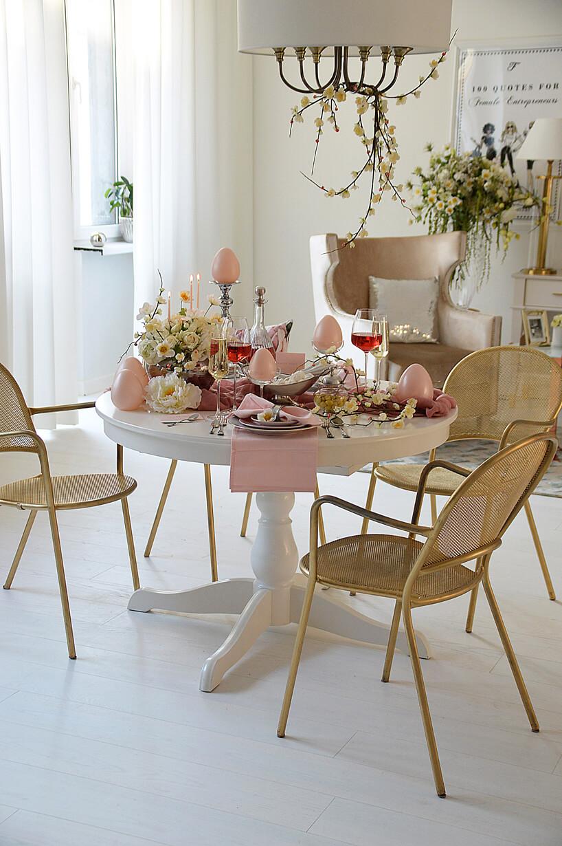 mały okrągły wielkanocny stół zastawiony wodcieniach różu wbiałej jadalni
