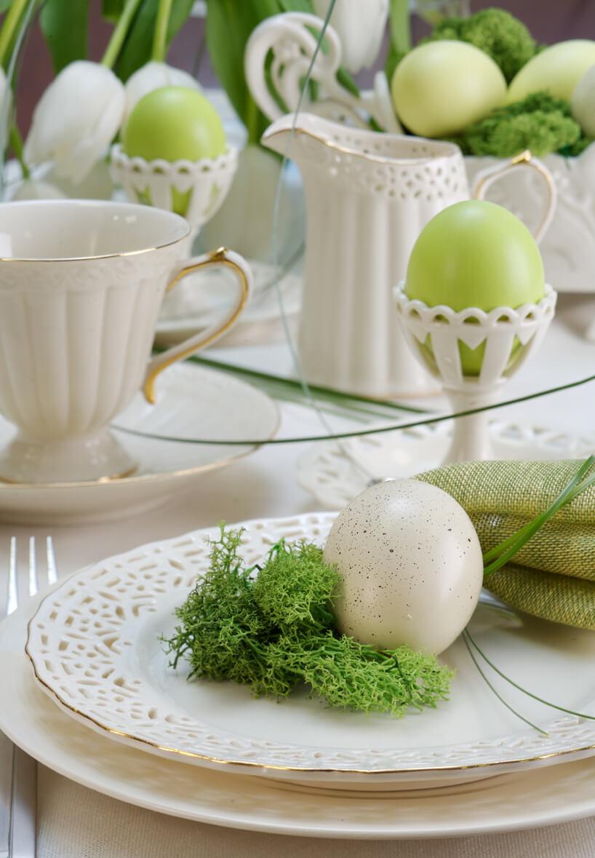 zastawiony stół wielkanocny białą ceramiczną zastawą zzielonymi dodaktami