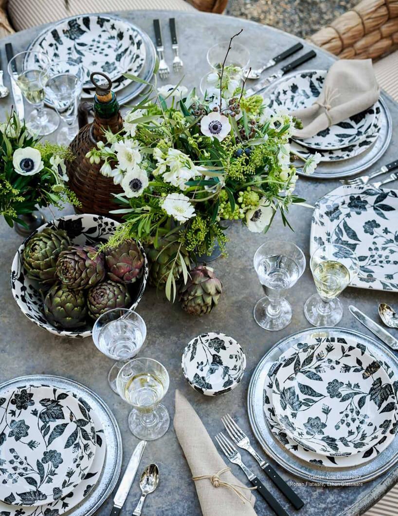 zastawiony stół zszarym obrusem iceramiczną zastawą wmotywach roślinnych