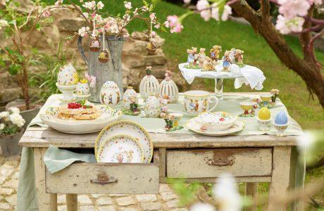 ceramiczne dodatki i zastawa wielkanocna na starym stole na tle ogrodu