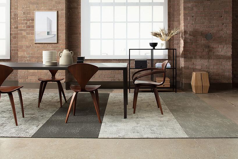 ciemny drewniany stół zczterema drewnianymi krzesłami na tle ściany zodsłoniętej cegły
