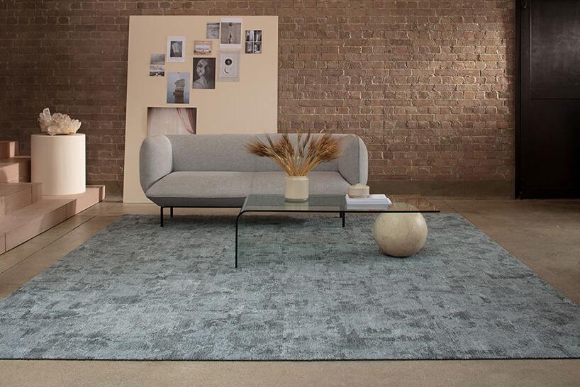 szara sofa przy stole zwygętej tafli szkła podparty kamienną kulą na tle ściany zodsłoniętych cegieł