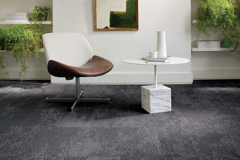 eleganckie krzesło zbrązowym siedziskiem ibiałym oparciem przy białym okrągłym stoliku zkamienną podstawą