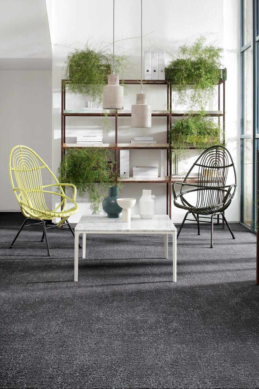 zółty ibrązowy fotel zmetalowych prętów przy białym stoliku zkamiennym blatem