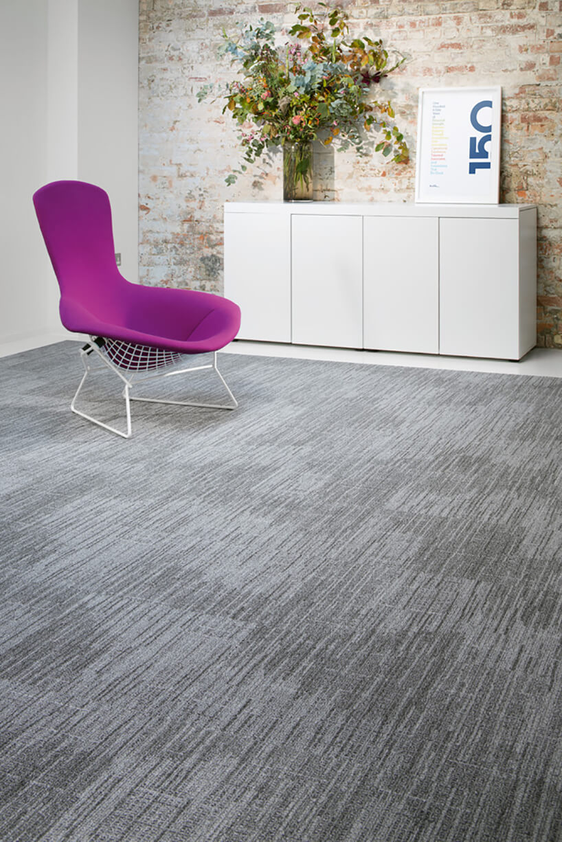 wyjątkowe fioletowe krzesło zbiałymi nogami na szarym dywanie na tle białej komody zdużym bukietem wszklanym wazonie