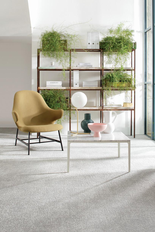beżowe krzesło zoparciami przy białym stoliku na tle półek zroślinami