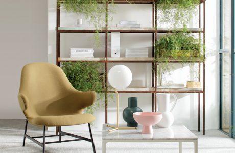 beżowe krzesło z oparciami przy białym stoliku na tle półek z roślinami