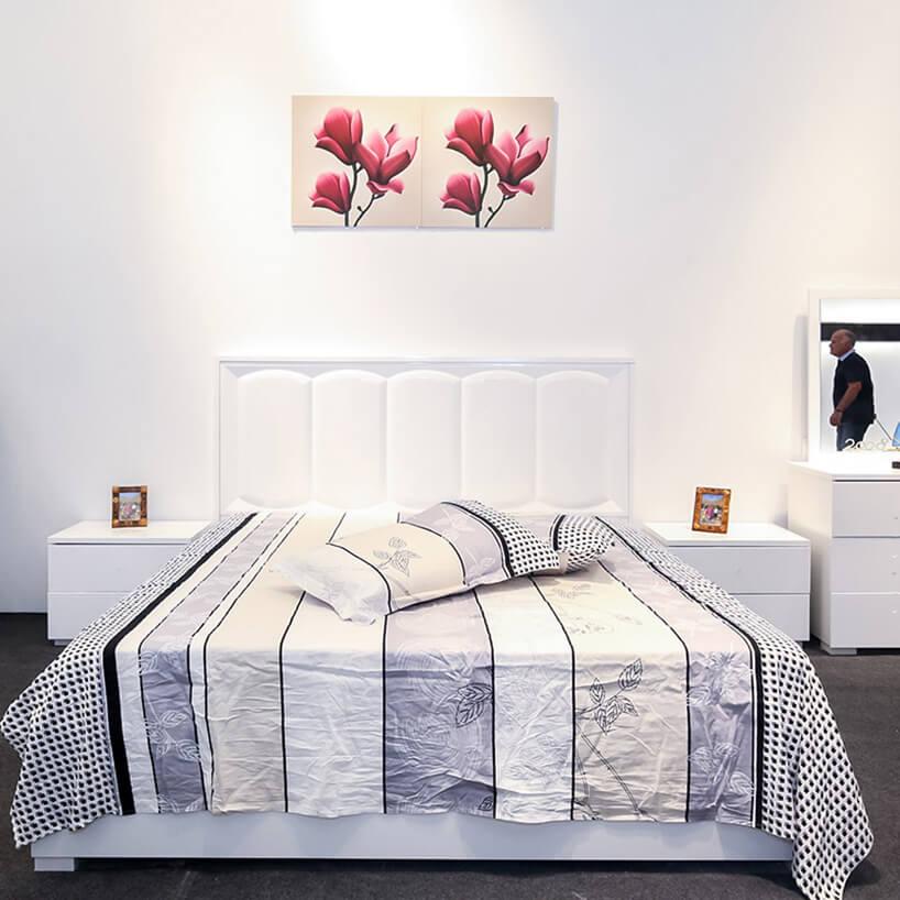 aranżacja stoiska na Furniture China 2018 zdużym białym łóżkiem idwoma małymi szafkami nocnymi