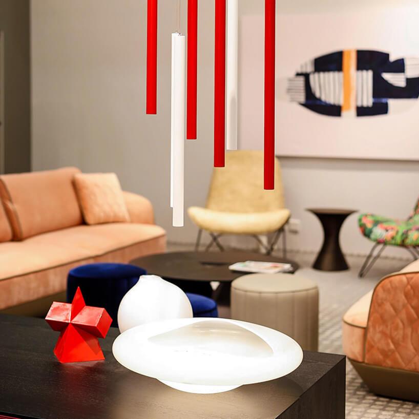 aranżacja stoiska na Furniture China 2018 zpastelowymi sofami czarnym stołem ipodłużną biało czerwoną lampą