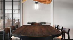 jadalnia zbrązowym zaokrąglanym stołem oraz krzesłami zjasnymi poduszkami pod lampa wkształcie chipsa
