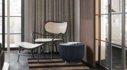 drewniany starszy fotel zbiałym materiałem oraz podnóżkiem stojącym na dywanie wzielono-kremowe pasy