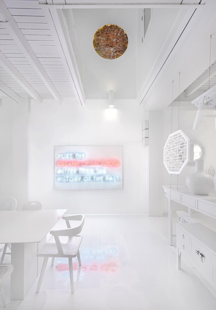 białe wnętrze przestrzeni co-livingowej ze stołem białym wysokim stołem