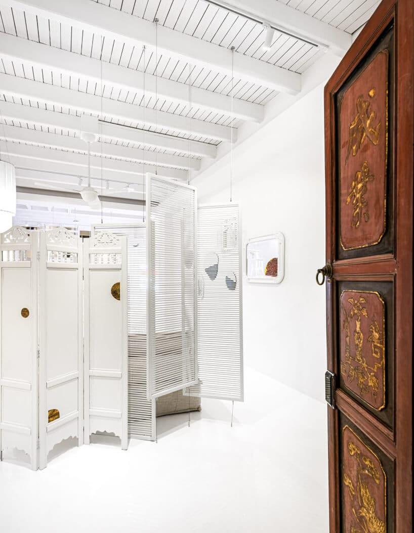 białe wnętrze przestrzeni co-livingowej białe parawany idrewniane zdobione drzwi