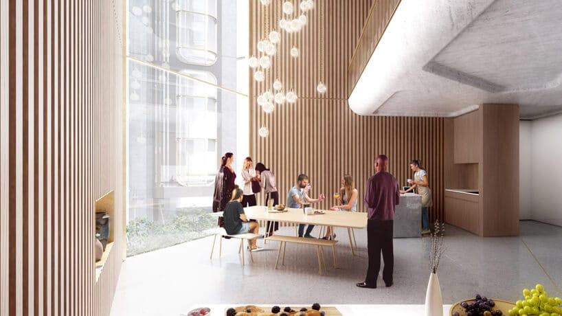 drewniane wnętrze przestrzeni co-livingowej duzy drewniany stół iludzie przy nim