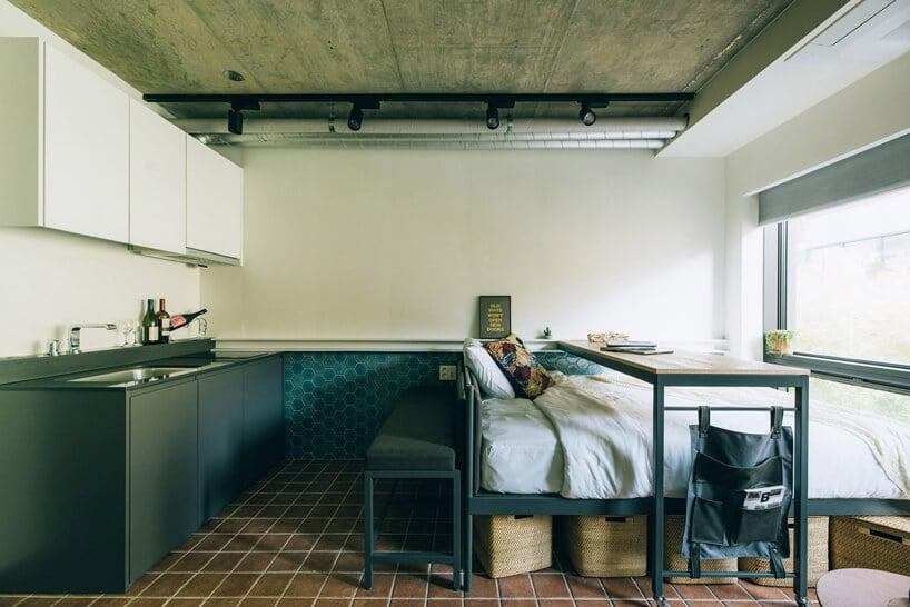 Przestrzeń co-livingowa małą kawalerka zzielonym aneksem kuchennym złóżkiem iprzesuwanym nad nim stolikiem