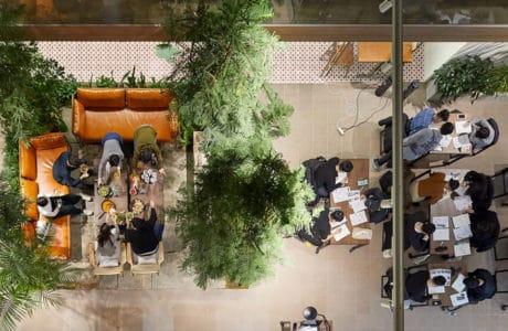 jasno brązowe wnętrze przestrzeni co-livingowej zdjęcie z góry na enklawy z siedziskami i ludzi przy nich