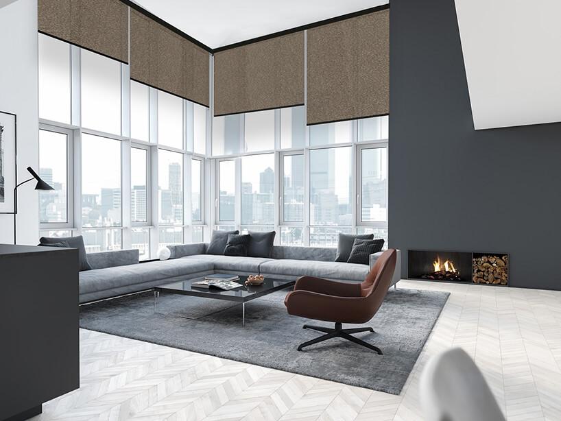 duży salon zdużą narożną sofą na tle ściany zokien zwysokimi brązowymi roletami
