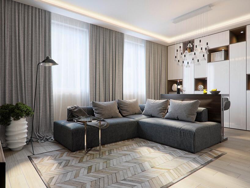 przytulny salon zszarą narożną sofą na tle okien ztrzema szarymi zasłonami