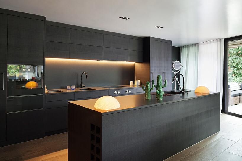 elegancka czarna kuchnia zdużą wyspą idużymi oknami na ścianie zbiałą izieloną cienką zasłonką