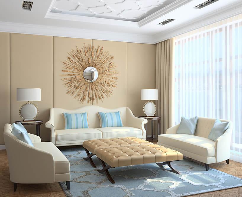 elegancki salon zniebieskim dywanem ztrzema kremowymi sofami na tle białych firanek zkremowymi zasłonami